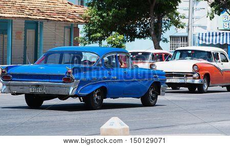 Varadero, Cuba - September 11, 2016:  Red and white American Classic Car Dirves in Varadero City, Cuba