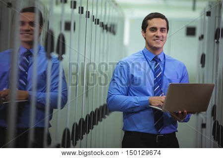 Portrait of technician using laptop while analyzing server in server room