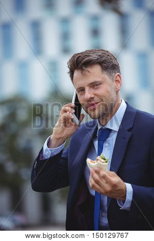 Portrait of handsome businessman eating snacks while talking on mobile phone