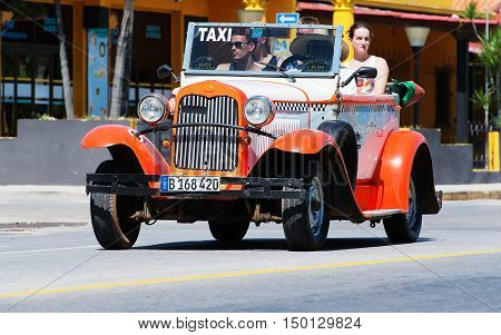 Varadero, Cuba - September 11, 2016:  orange American Cabriolet Classic Car Dirves in Varadero City, Cuba