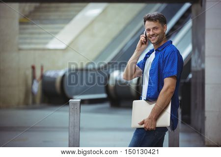 Handsome man holding laptop and talking on mobile phone at railway station