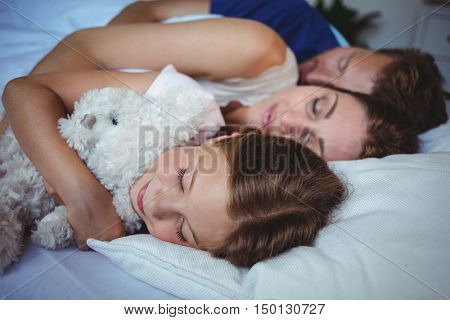 Family sleeping on bed at home