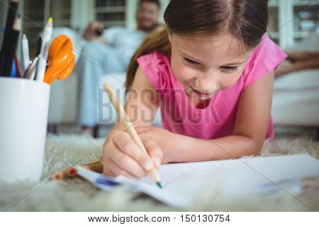 Smiling girl lying on the floor and drawing while parents sitting on sofa