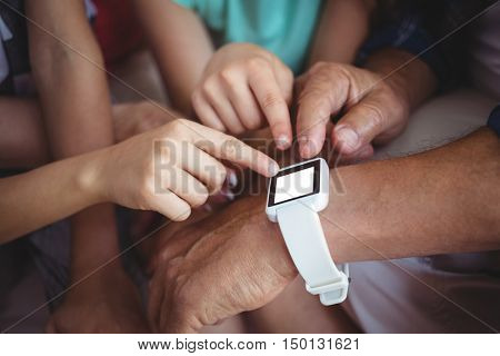 Close-up of family pointing at smart watch