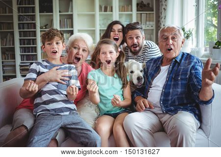 Happy family watching television in living room at home