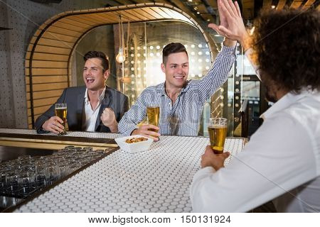 Friends giving high five while watching tv in bar