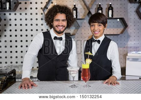 Portrait of smiling waitress and waiter standing in bar counter with glass of cocktail at bar