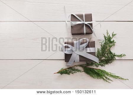 Lots of gift boxes and fir tree branches on white wood background. Stylish modern presents in dark paper decorated with satin ribbon bows. Christmas and winter holidays concept, top view, copy space