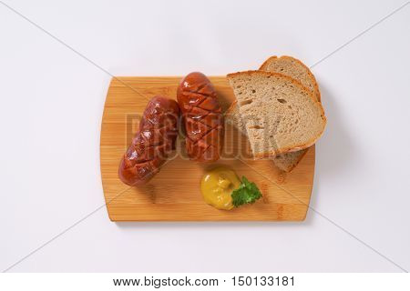 short thick sausages with slices of bread and mustard on wooden cutting board
