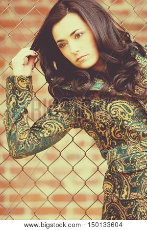 Beautiful woman leaning against iron fence