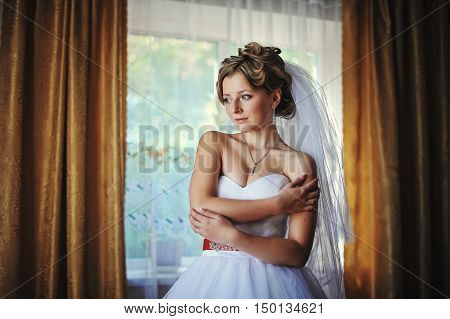Young bride posing against the backdrop curtains