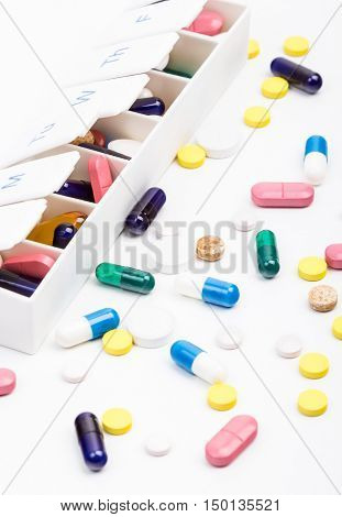 Color pills and capsules in and out of pill organizer portrait view