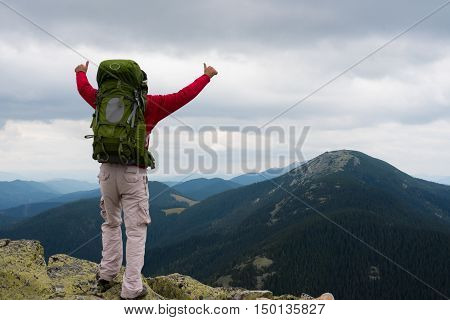 Happy tourist standing with backpack on a mountain top with raised up hands. Concept of success . Happy hiker winning reaching life goal success freedom and happiness achievement in mountains.Thumbs-up