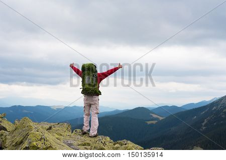 Happy tourist standing with backpack on a mountain top with raised up hands. Concept of success . Happy hiker winning reaching life goal success freedom and happiness Thumbs-up