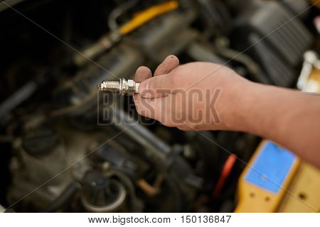 Man Fixing new spark plug in yellow car.