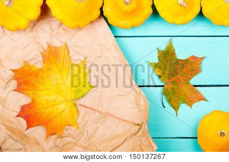 Pumpkins and maple leaves on a wooden table
