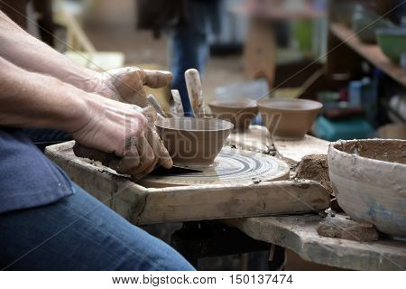 potter creating a new ceramic made of clay on the potter's wheel in the pottery selected focus and narrow depth of field