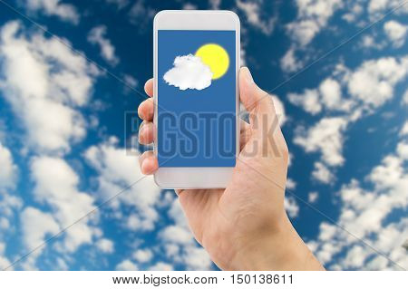 Detail of hand consulting the prediction weather with the smartphone with clouds and sky in background. All screen content is designed by me and not copyrighted by others and created with wacom tablet and ps