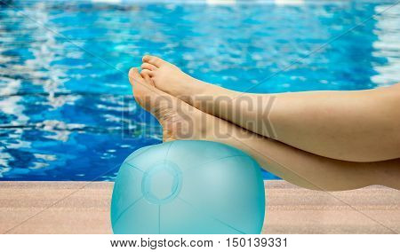 relaxed person with feet above the ball on the pool