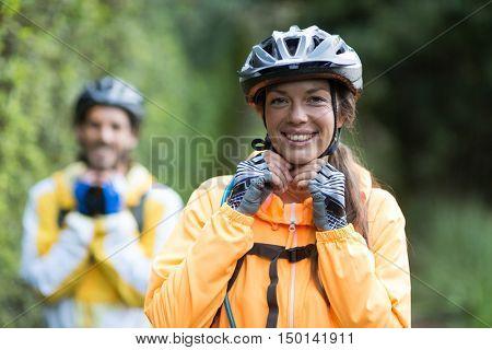Portrait of female biker wearing bicycle helmet in countryside