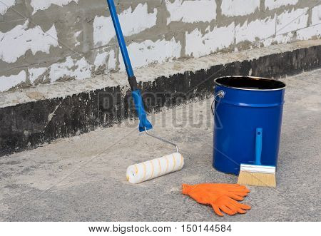 Ceiling brushes Brushes and a bucket of bitumen primer for waterproofing against the background of a brick wall