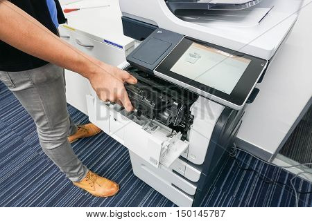 businessman put the ink cartridge into printer