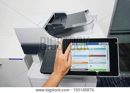 woman use touch screen of printer for copying documents