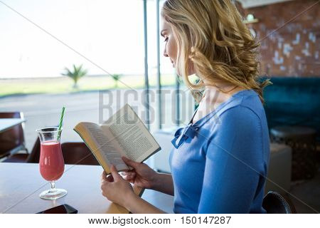 Woman reading a novel in the coffee shop