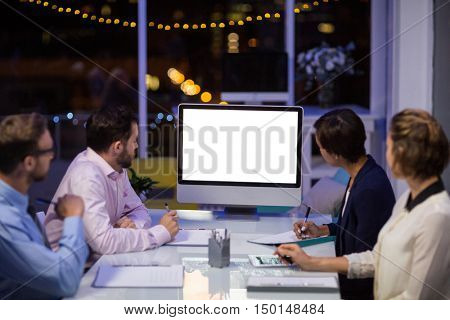 Businesspeople looking at computer in conference room at office