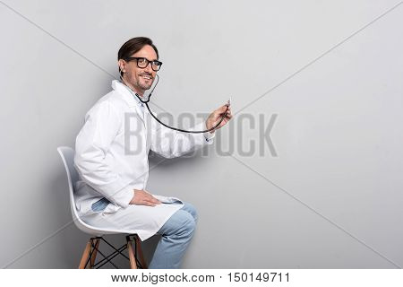 Ready to help. Joyful young handsome doctor using a stethoscope while sitting on a chair beyond grey background and diagnosing the patient