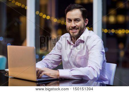 Portrait of happy businessman using laptop