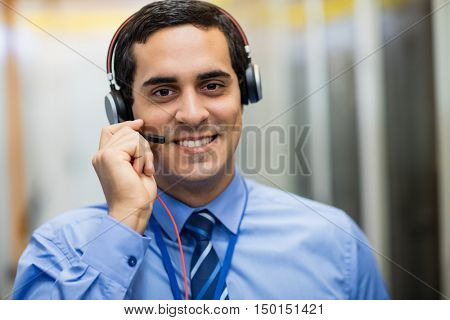 Portrait of happy technician talking on head phones