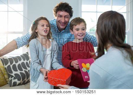 Children giving present to their mother at home