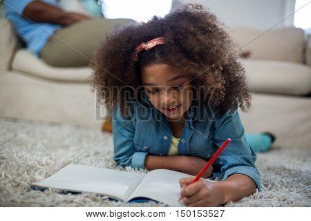 Girl doing homework while lying on the floor at home