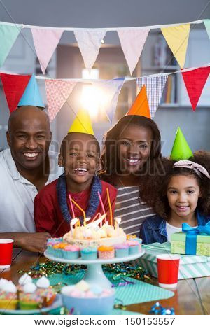 Portrait of family with birthday cake at home