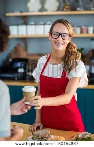 Portrait of waitress serving a coffee to customer at counter in caf\x92\xA9