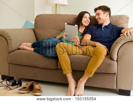 Young couple sitting on the sofa and watching something on a tablet