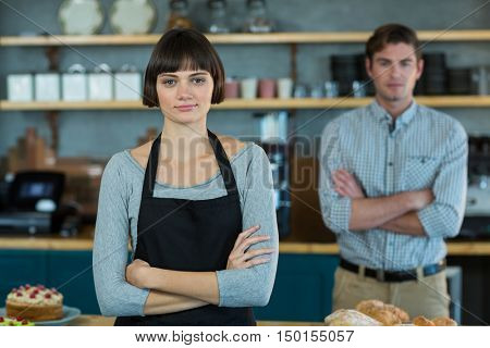 Portrait of waitress standing with arms crossed in cafe