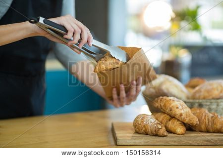 Mid-section of waitress packing croissants in paper bag at caf\x92\xA9