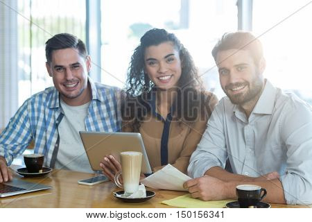 Portrait of smiling friends using digital tablet and laptop in caf\x92\xA9