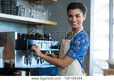 Portrait of smiling waitress making cup of coffee in cafe