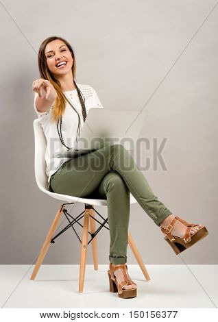 Beautiful woman sitting on a chair  with a laptop and pointing to the camera