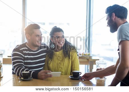 Waiter serving a cup of coffee to customer in cafe