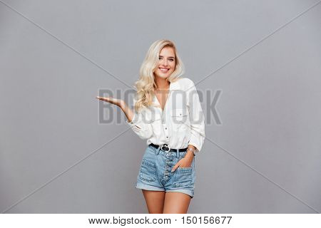 Smiling happy girl holding copyspace on the palm isolated on a gray background
