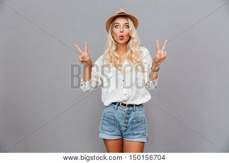 Funny excited young woman showing peace sign over gray background