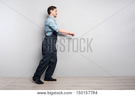Work with enthusiasm. Pleasant senior deligent man holdign truck and workign while walking along grey wall