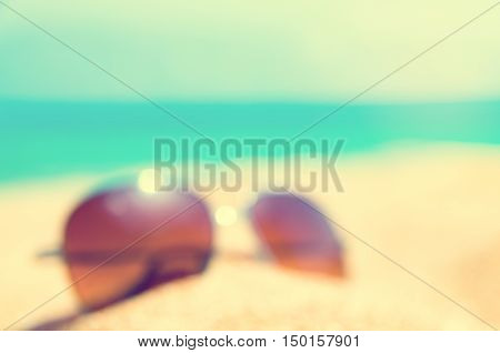 blurred abstract Fashion sunglass on the summer beach at ocean background vintage filter Summer vacation actually relaxing summer concept vocation time summer background