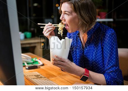 Businesswoman eating noodles at her desk in the office