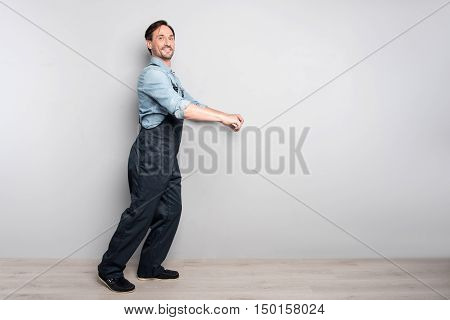 Real worker. Pleasant delighted diligent man holdign truck and smiling while standing isolated on grey background