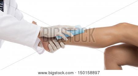 Medical doctor holding ice pack on ankle isolated on white background.